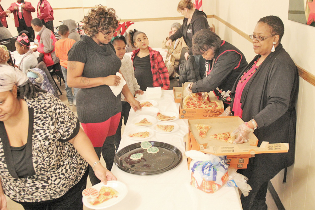 Attendants go through pizza line at the Christmas party.