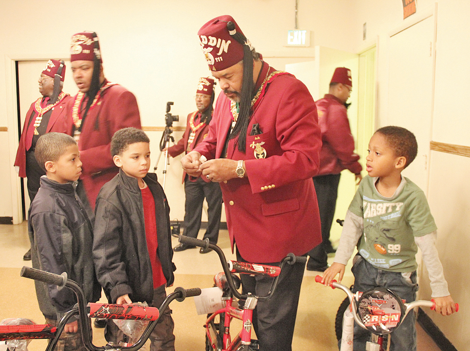 Walter Starkey presents bikes to several happy kids.