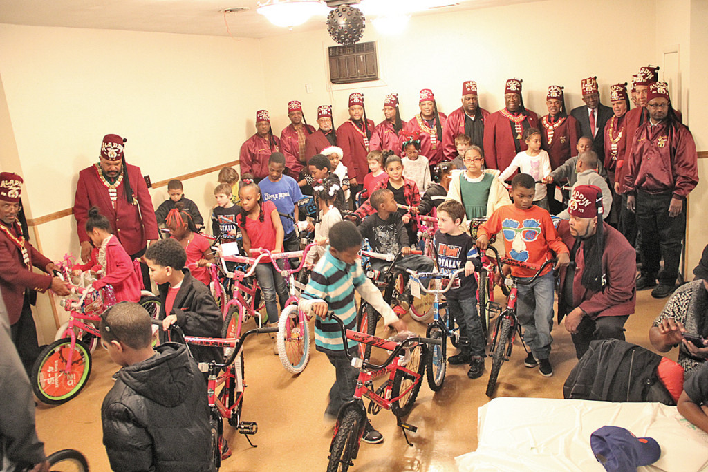 Shriners pose with kids on their new bikes at the annual Christmas Party held at the Aladdin Temple #111 on Saturday, Dec. 20, 2014.   – Photos by S. Hale