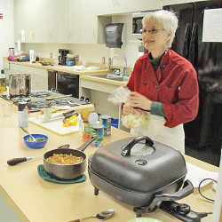 Chef Laura Pole preparing African Heritage Spicy Chickpeas and Jollof Rice in the New Horizons Healthcare kitchen.