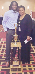 Warren Craft and mother Toni Brown stand behind Athletic and Achievement Award trophy.