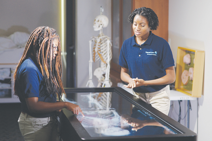 STUDENTS: Kenya Swilling, at left, and Kaia Amoah learn to operate the Virginia Tech Carilion School of Medicine's virtual anatomy table.